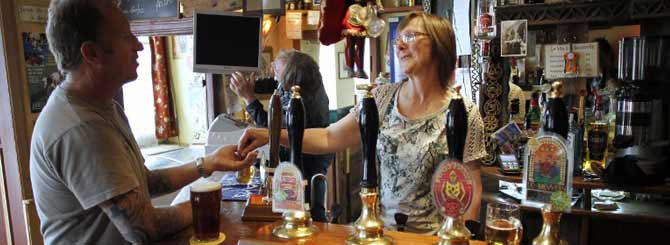 Jane Skews chats with a customer as she pours craft beer at The Famous Knight