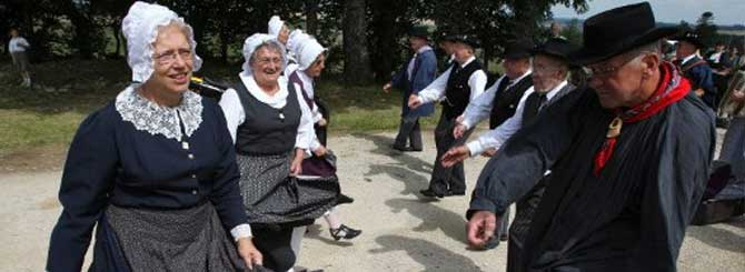 Locals in traditional costumes welcome Tour de France cyclists racing from Chablis to Autun